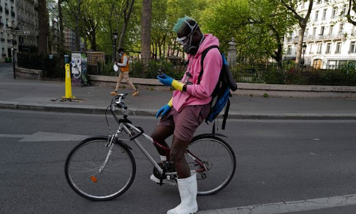 A man on a bike checking his phone.